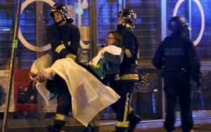A halálos párizsi lövöldözést követően a francia tűzoltóbrigád tagjai egy sérültnek segítenek a Bataclan koncertterem mellett